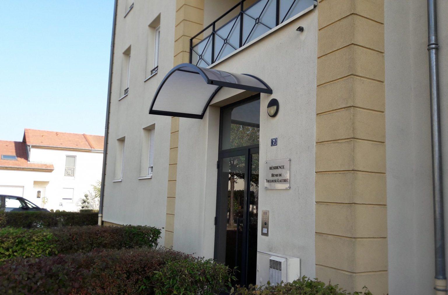 Un auvent pour la couverture d'une entrée d'immeuble en polycarbonate granité, RAL 9005 Satiné, Label qualicoat
