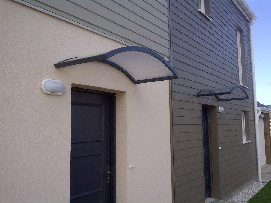 Auvents épurés en aluminium cintré L1,4 x Prof 0,7. sur façades de maisons mitoyennes. Habillage en polycarbonate granité et ossatures monoblocs grises.