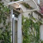 Une marquise de porte pour maison en aluminium cintré et autoporteuse. Monture bombé de couleur blanche.