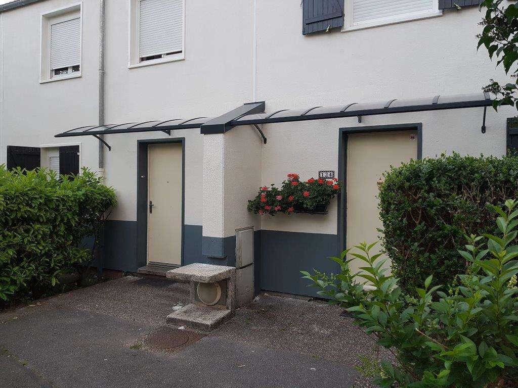 Marquise auvent aluminium L 5600 x P 1000 sur une façade de 2 maisons mitoyennes protégeant 2 portes, son ossature est grise et son remplissage en polycarbonate