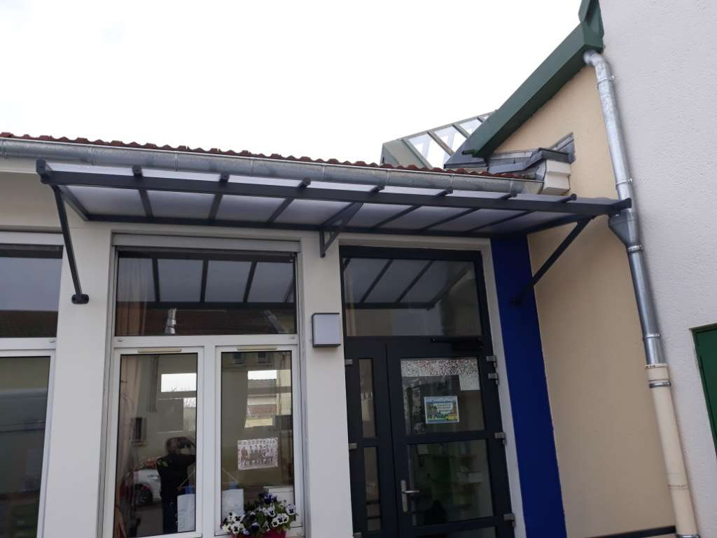 Couverture de porte en alu pour école élémentaire protégeant une porte fenêtre et une fenêtre, en aluminium soudé et thermo laqué noir, remplissage en polycarbonate granité 4mm