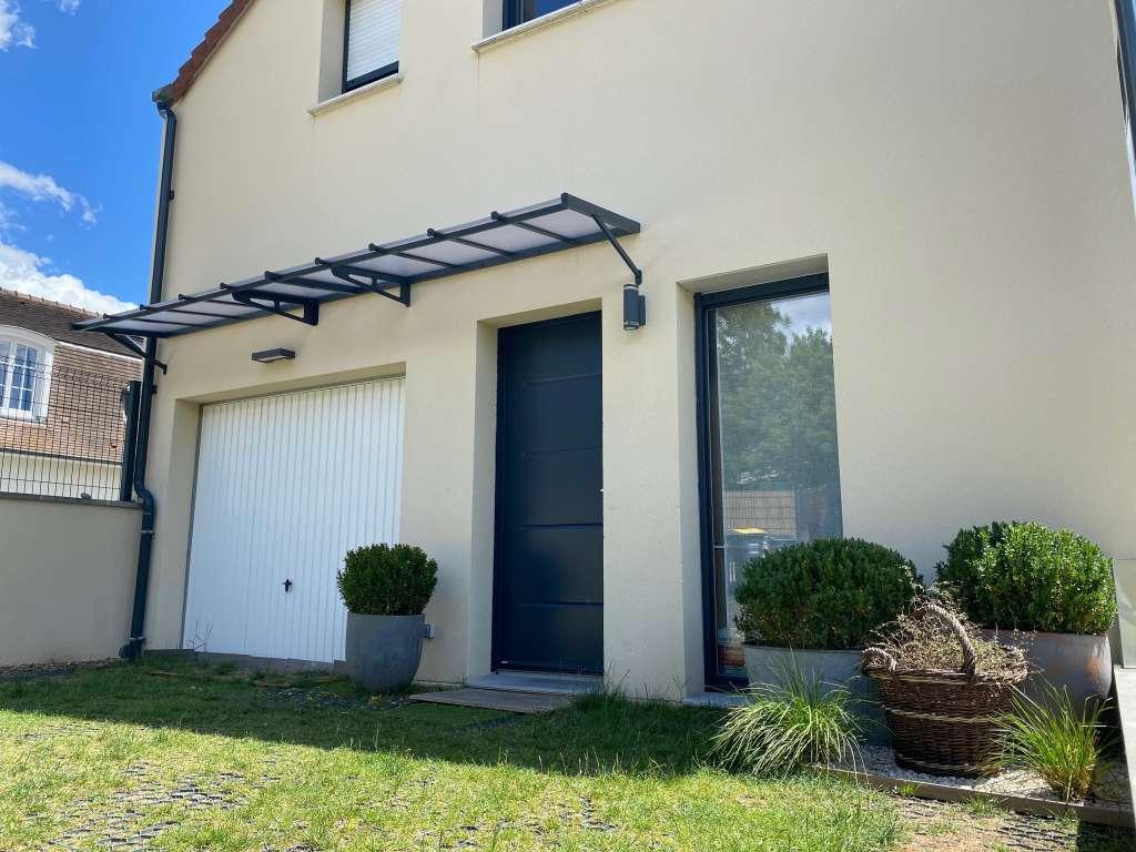 Auvent double portes de 4,8 mètres protégeant la porte d'entrée et la porte de garage. Marquise en aluminium noir soutenue par 2 équerres intermédiaires et 2 jambages latéraux