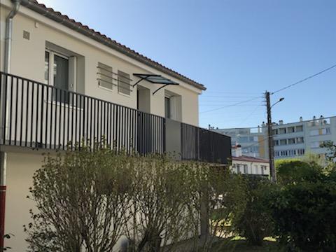 Marquise de porte en aluminium au 1er étage d'un bâtiment jaune. Structure de largeur 1200 par profondeur 940 avec jambages cintrés,
