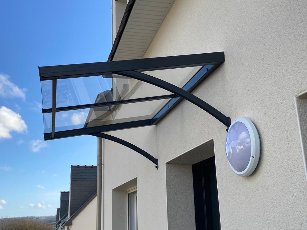 Abri de porte d'entrée en aluminium noir et 2 verres trempé incolore de 4mm, jambages cintrés. L1400 X PROF 940